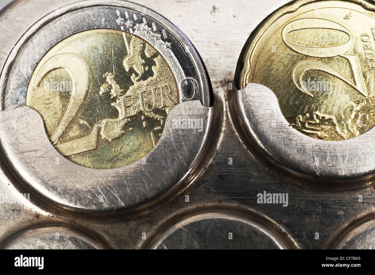 two euro coins and twenty cents in old coin receptacle - Stock Image