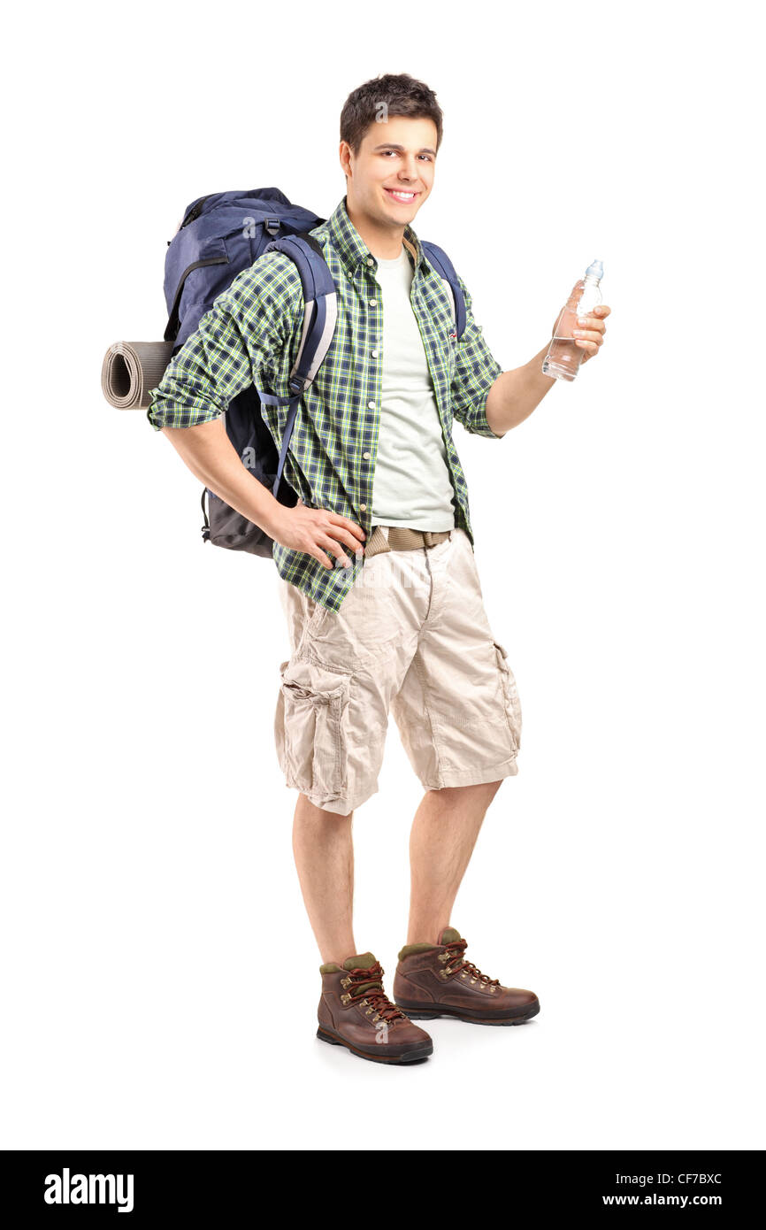 Full length portrait of a young hiker holding a bottle of water isolated on white background - Stock Image