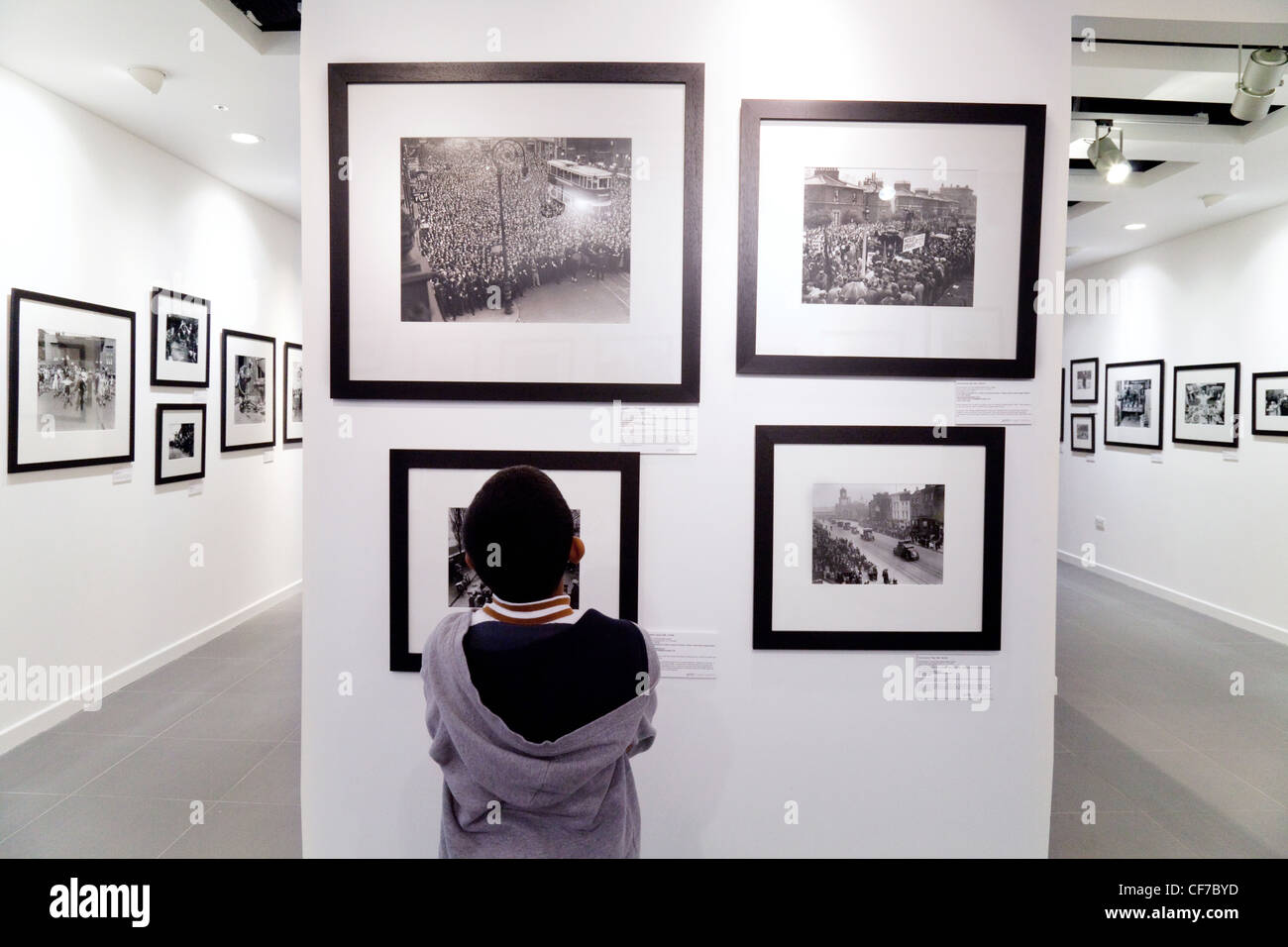 A child looking at photos in the Getty gallery, Westfield shopping centre Stratford London UK - Stock Image