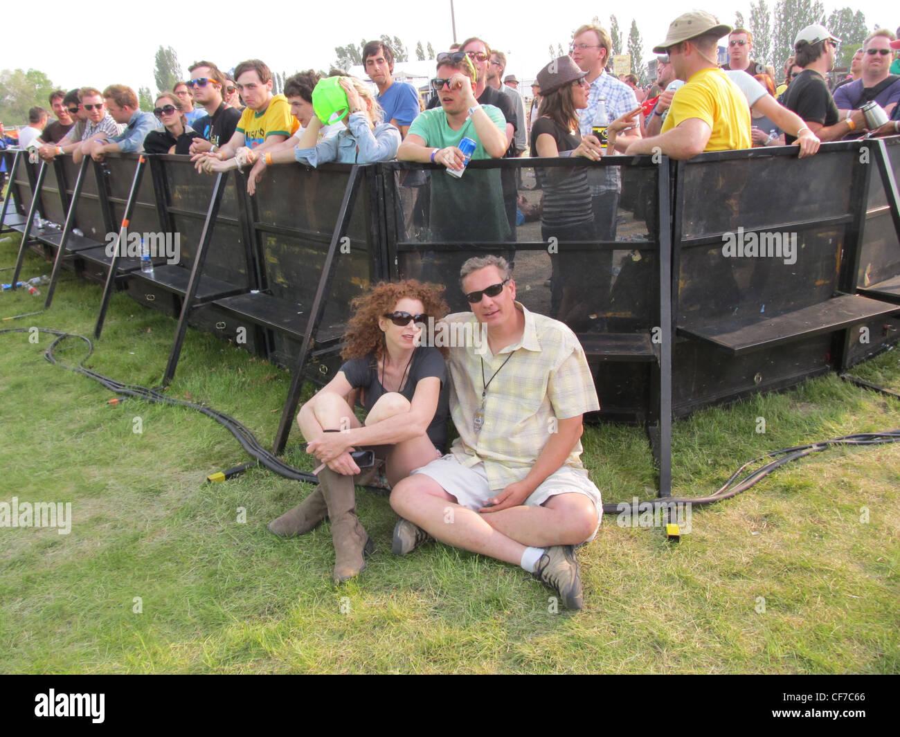 Two people sitting in VIP media area at a music festival, separated by barricade from general admission crowd. - Stock Image