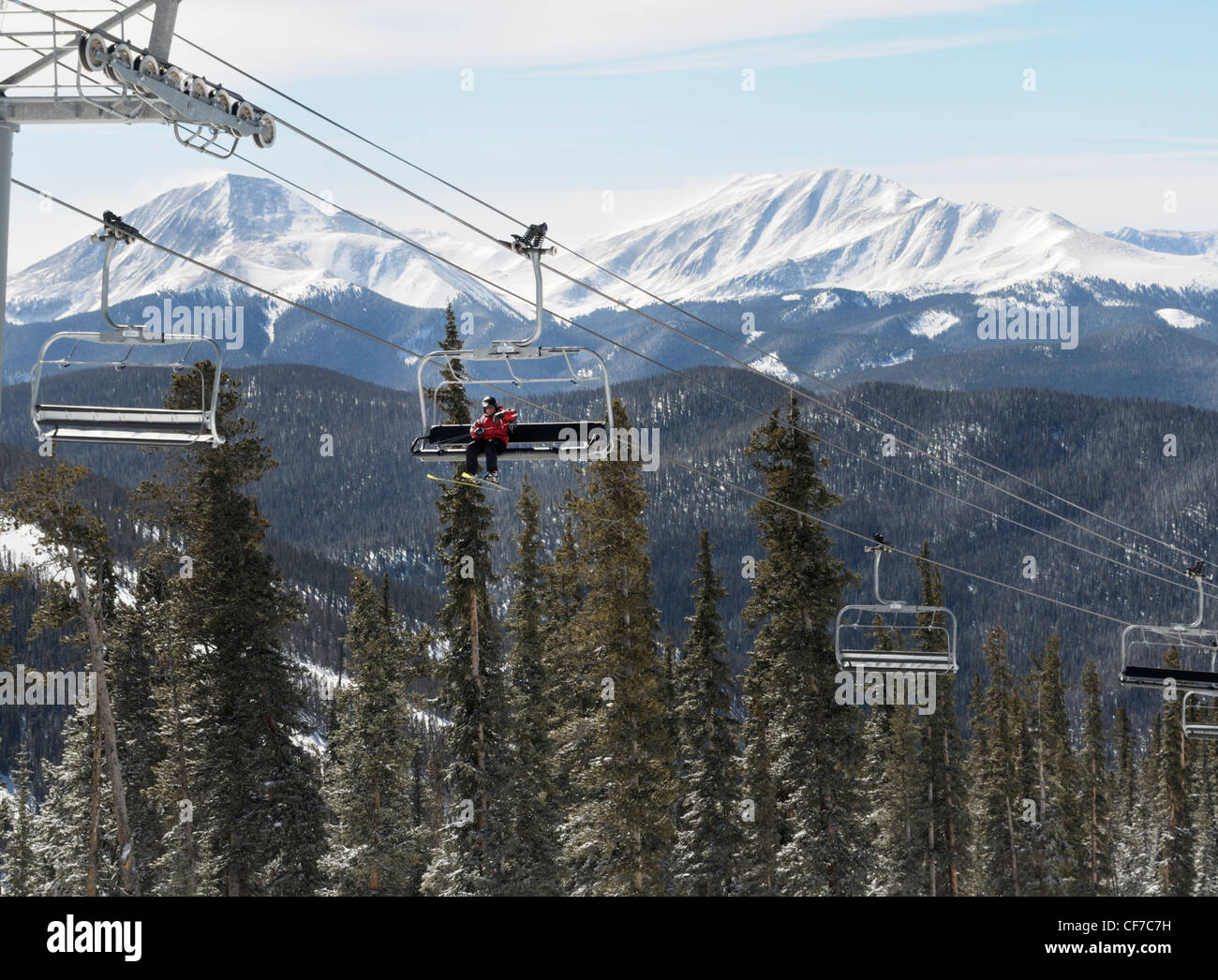 Chairlift bringing lone skier to the summit, Keystone Resort, Colorado - Stock Image