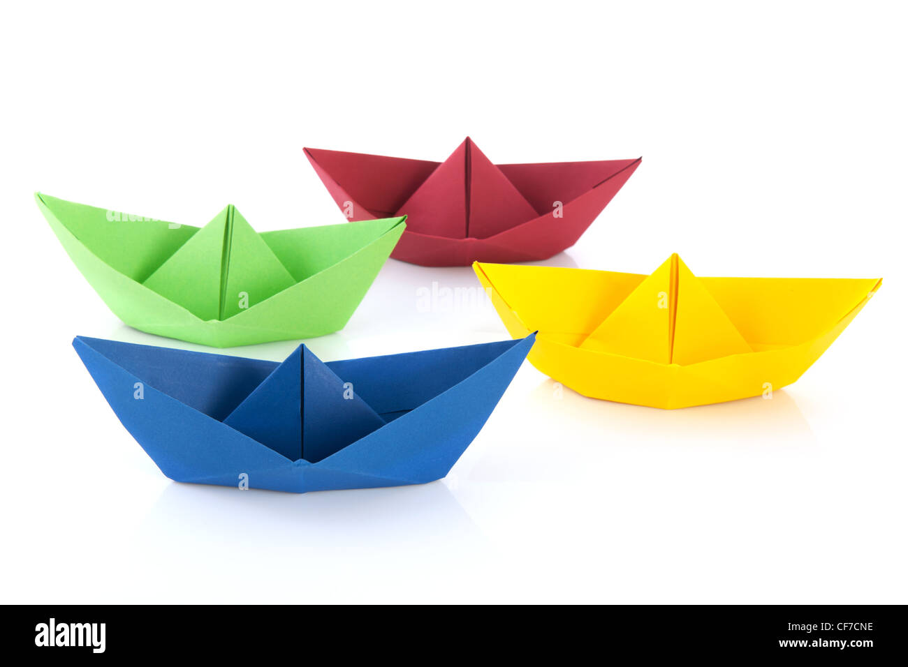 Colorful folded paper boats isolated over white background - Stock Image