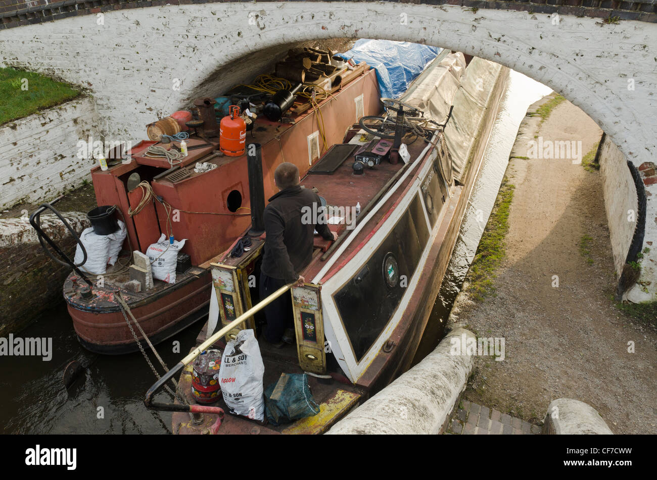 One man guiding two narrow boats under a canal bridge at Stockers Lock Grand Union canal Rickmansworth Herts UK - Stock Image