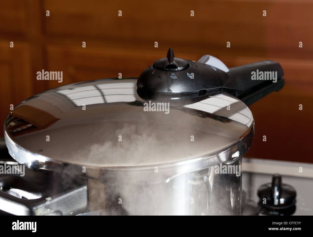 Pressure cooker releasing steam pressure on hob in modern kitchen - Stock Image