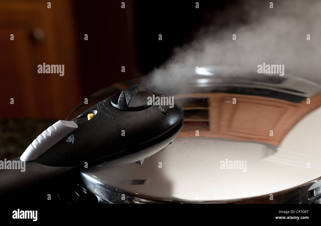 Steam escaping from lid of pressure cooker with reflection of modern kitchen - Stock Image