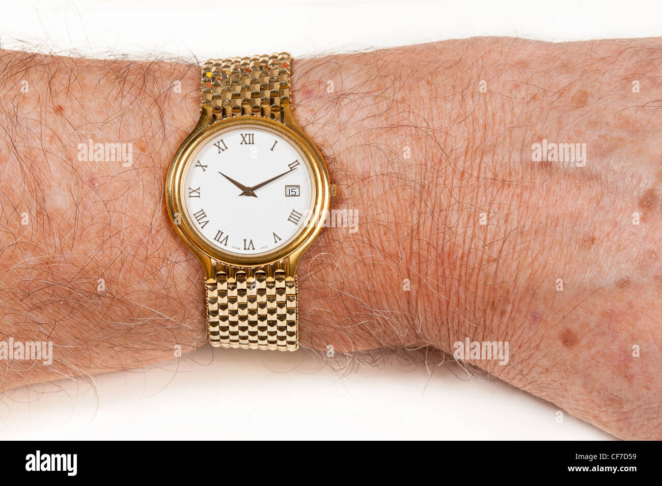 Gold watch and band in close up on wrist of hairy senior man - Stock Image