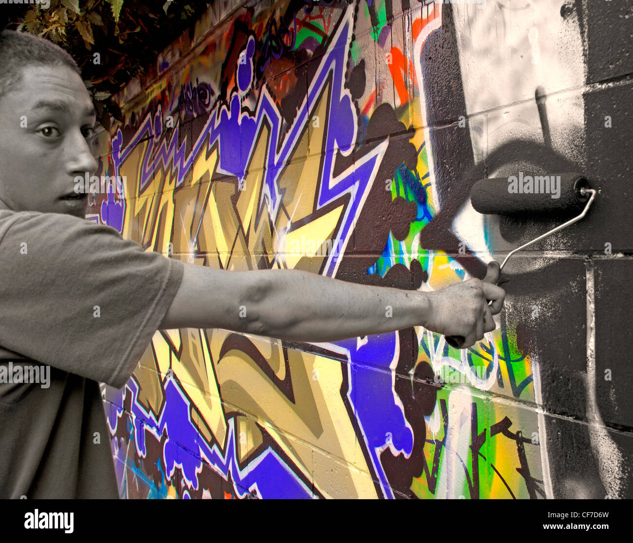 Removing colourful graffiti with a paint roller covered in black paint, Potterrow, Edinburgh, Lothian, Scotland, - Stock Image
