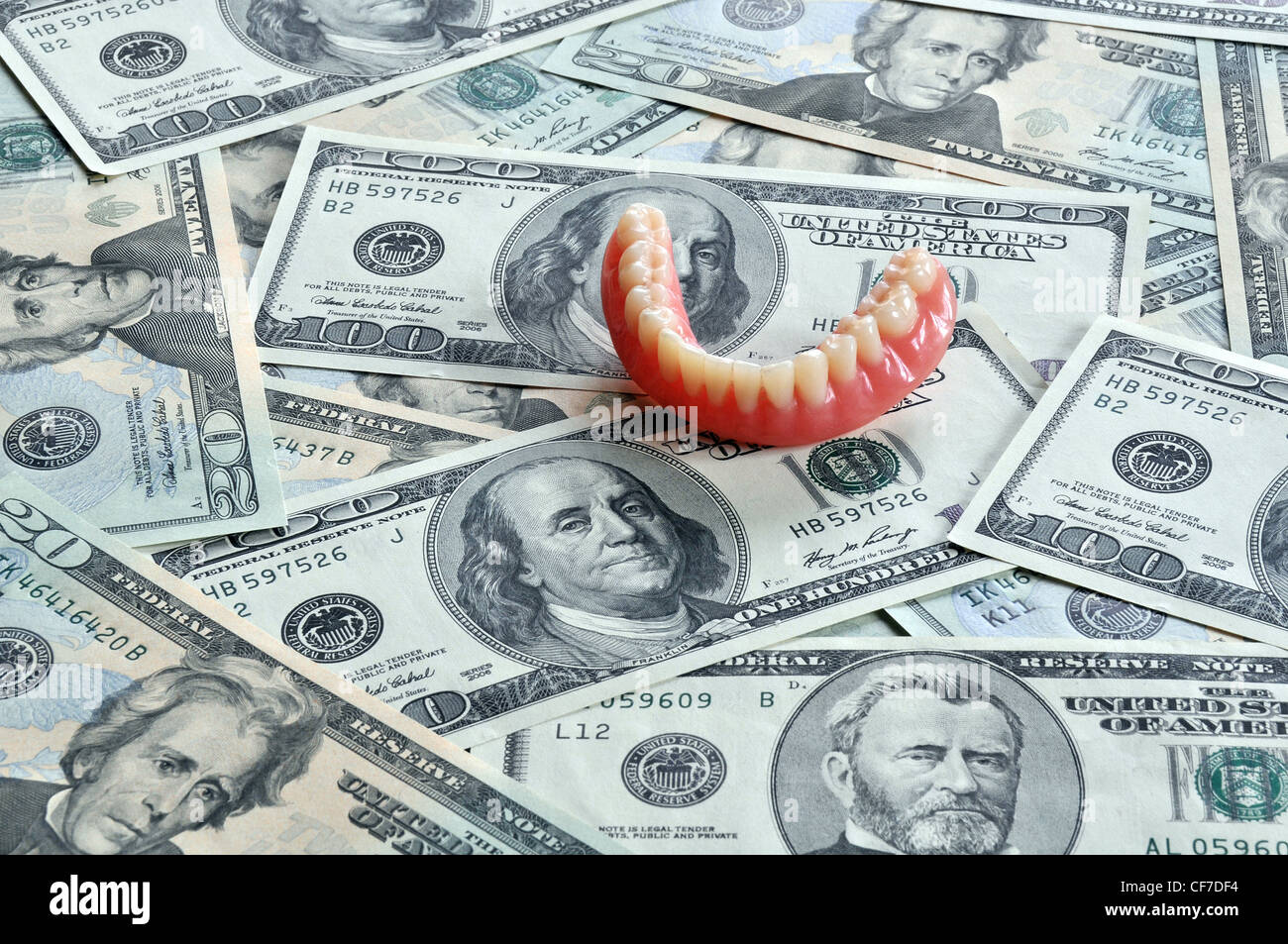 denture on dollar notes - Stock Image
