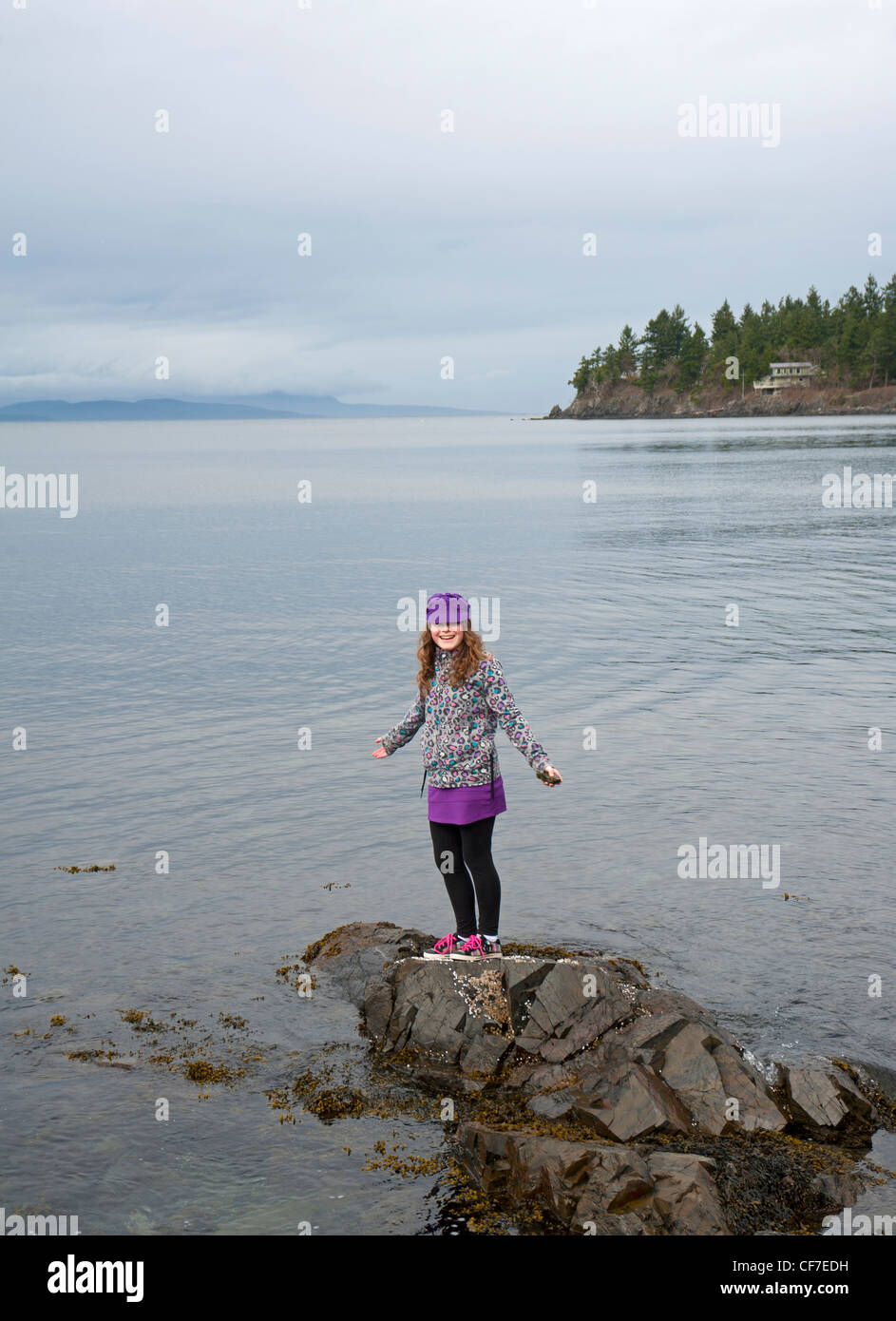 Young girl on the rocks by the seaside, Seacreast Nanoose. Vancouver Island. British Columbia. Canada. SCO 8065 - Stock Image
