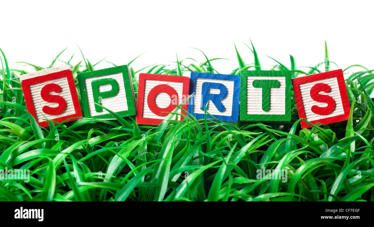 Alphabet blocks forming SPORTS on a patch of grass - Stock Image