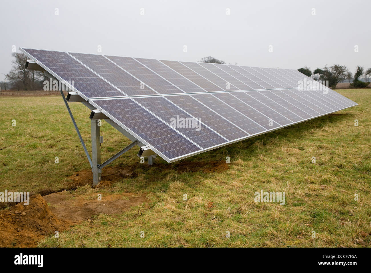 Array of photovoltaic panels stands in field - Stock Image
