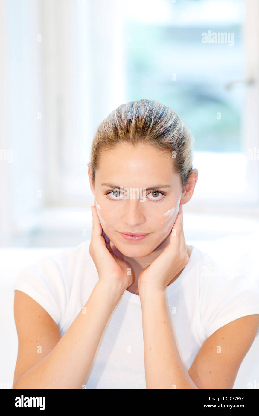 Female highlighted fair hair off her face, wearing a white t shirt, applying face cream to her cheeks, unsmiling, - Stock Image