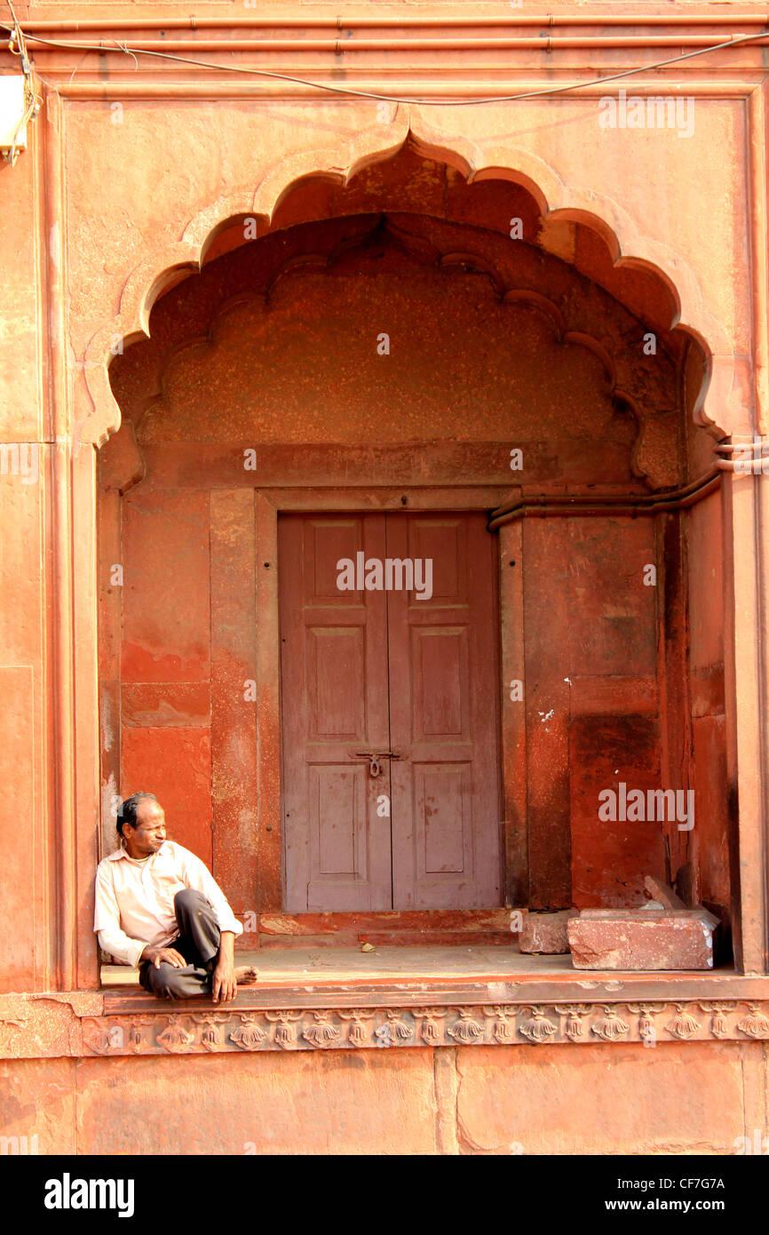 Man sitting by an arch at the Juma masjod, Delhi, India - Stock Image