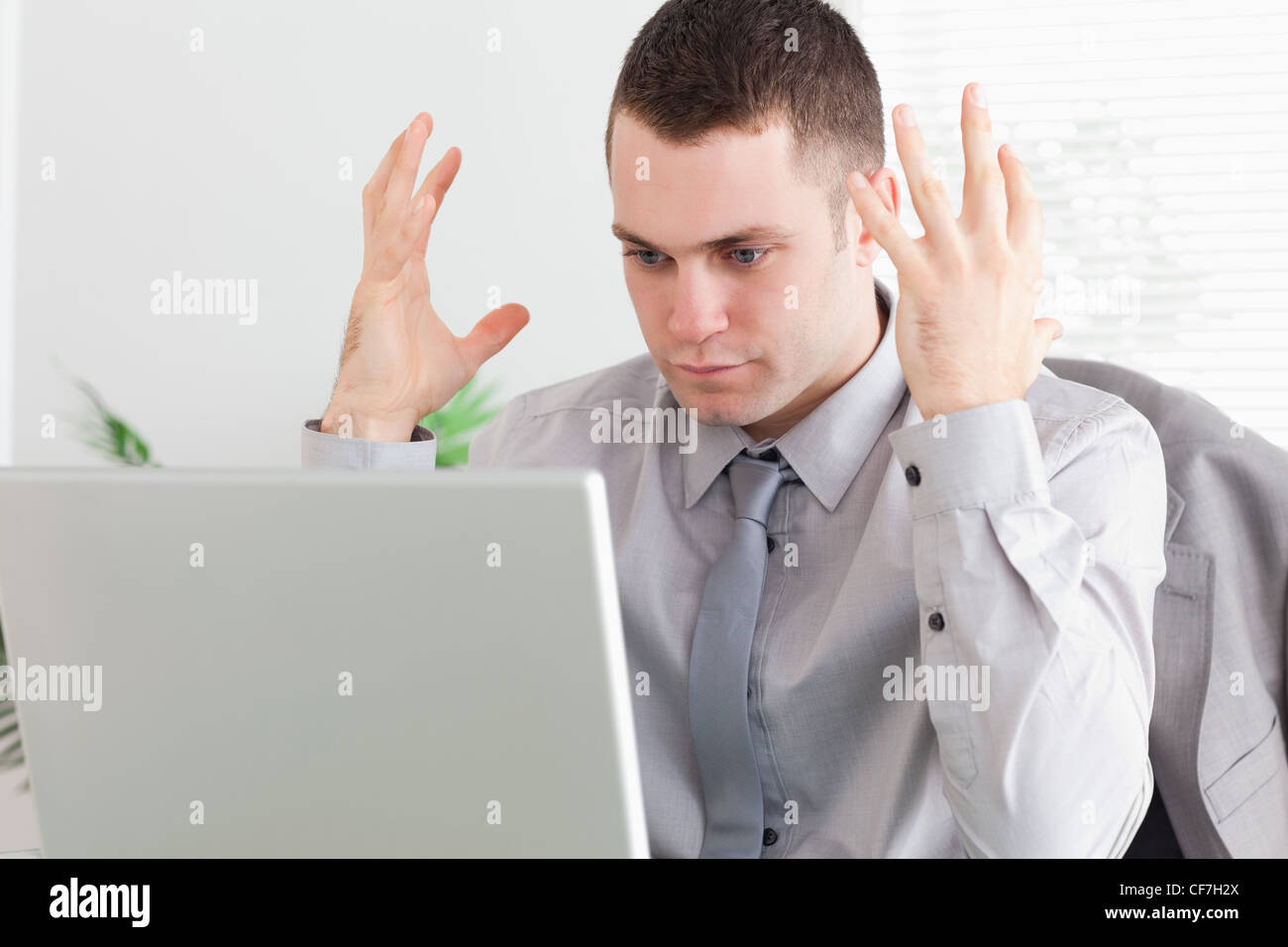 Close up of businessman experiencing problems with his laptop - Stock Image