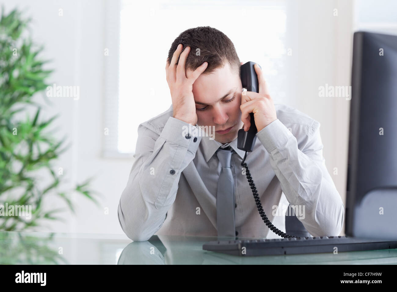 Close up of businessman getting bad news on the phone - Stock Image