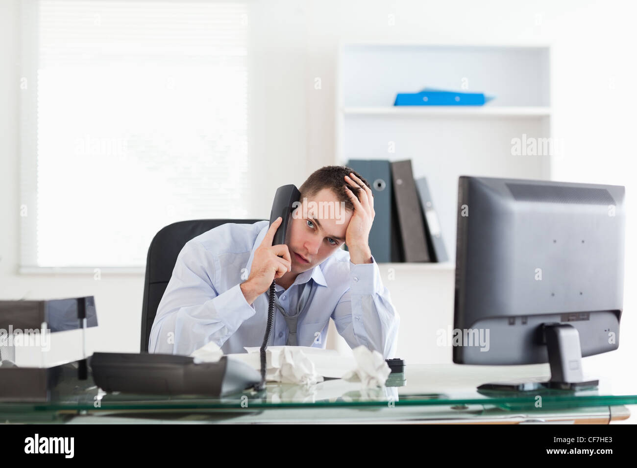 Businessman trying to solve a problem on the phone - Stock Image