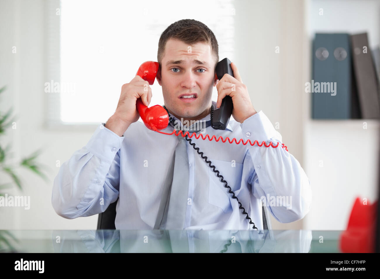 Businessman unable to cope the telephone - Stock Image