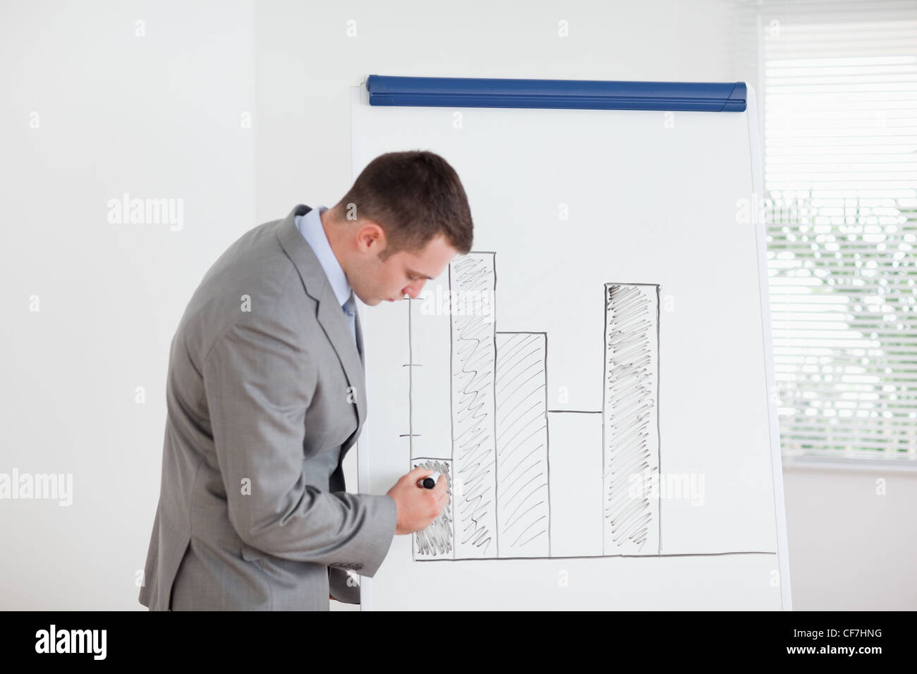 Businessman editing column graph - Stock Image