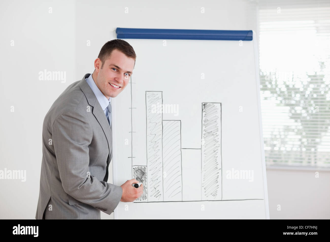 Smiling businessman editing column graph - Stock Image