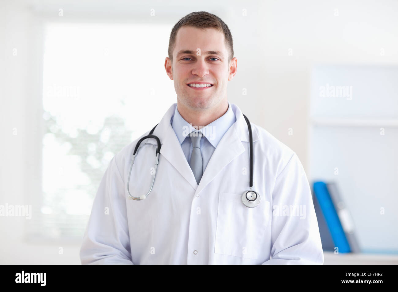Smiling doctor in his practice - Stock Image