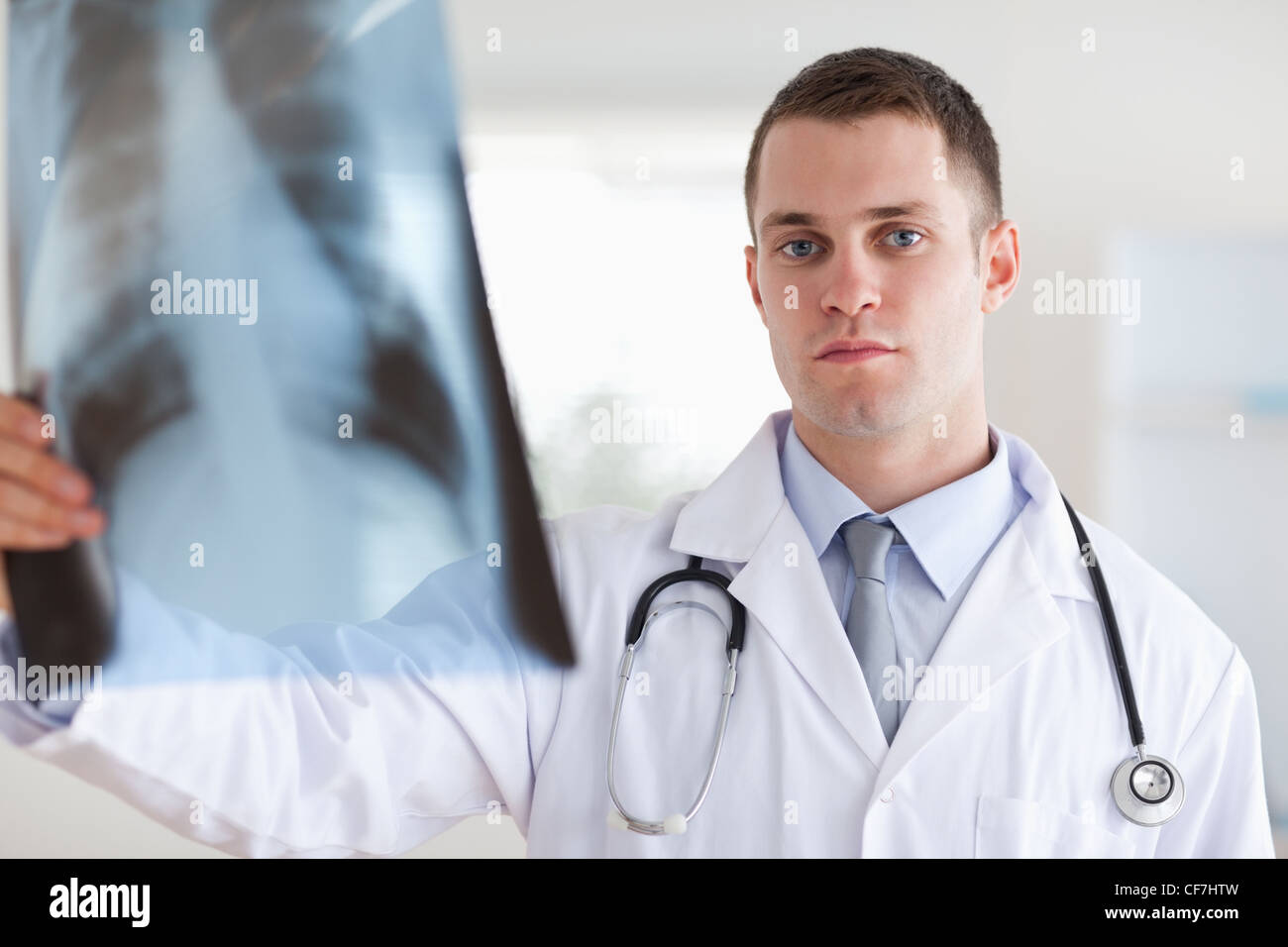 Serious looking doctor with x-ray - Stock Image