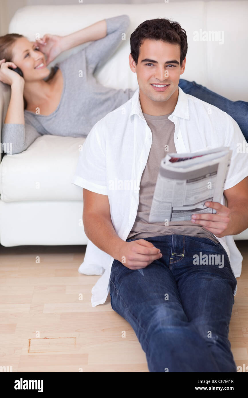 Man leaning against the sofa with newspaper while his girlfriend listens to music - Stock Image