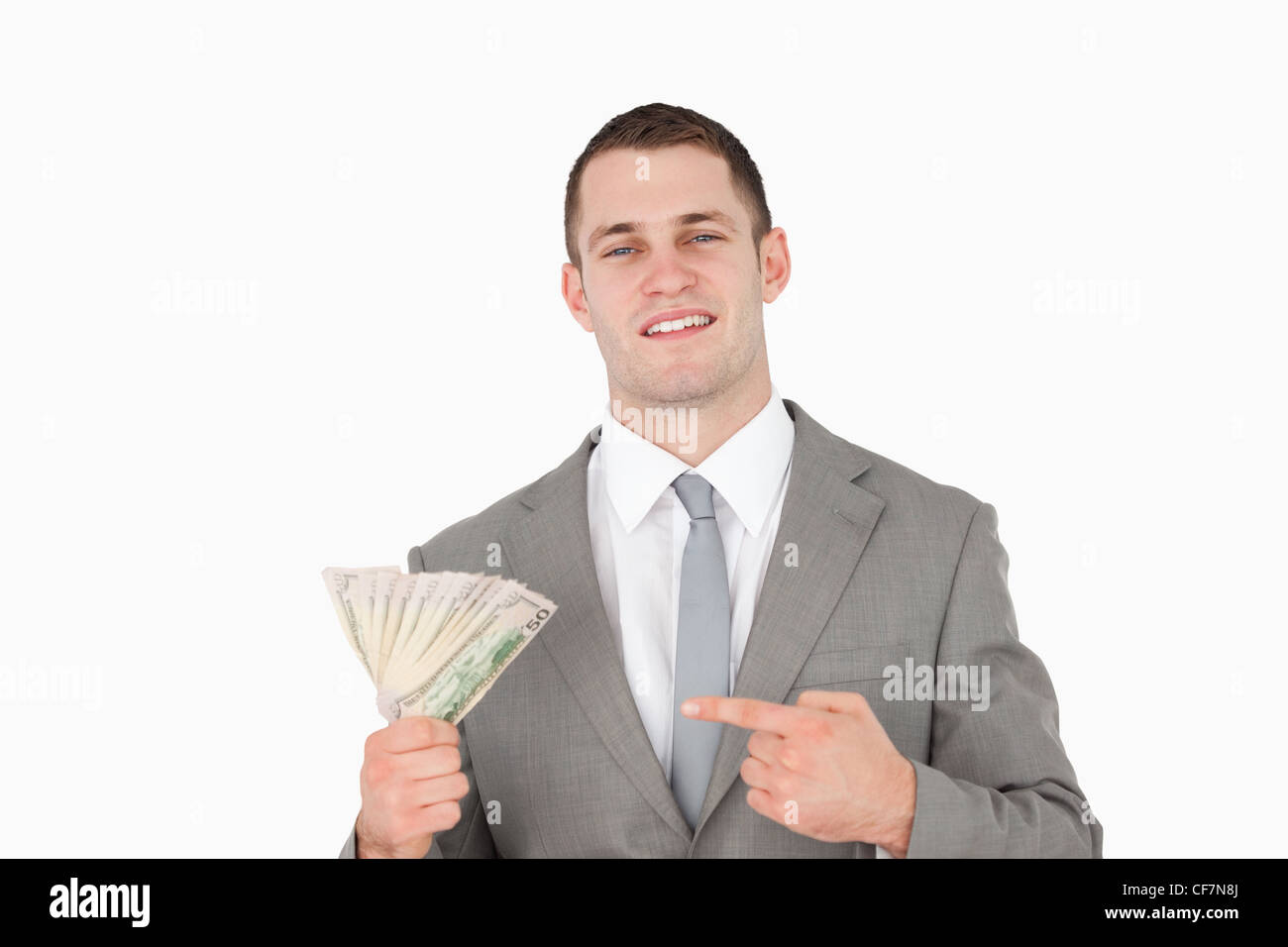 Businessman pointing at a wad of cash - Stock Image