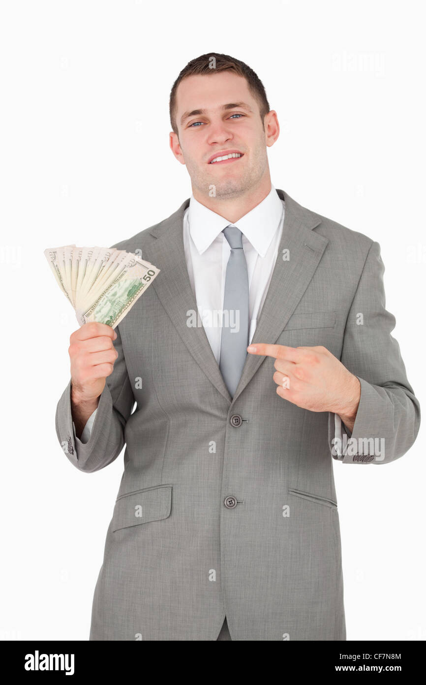 Portrait of a businessman pointing at a wad of cash - Stock Image