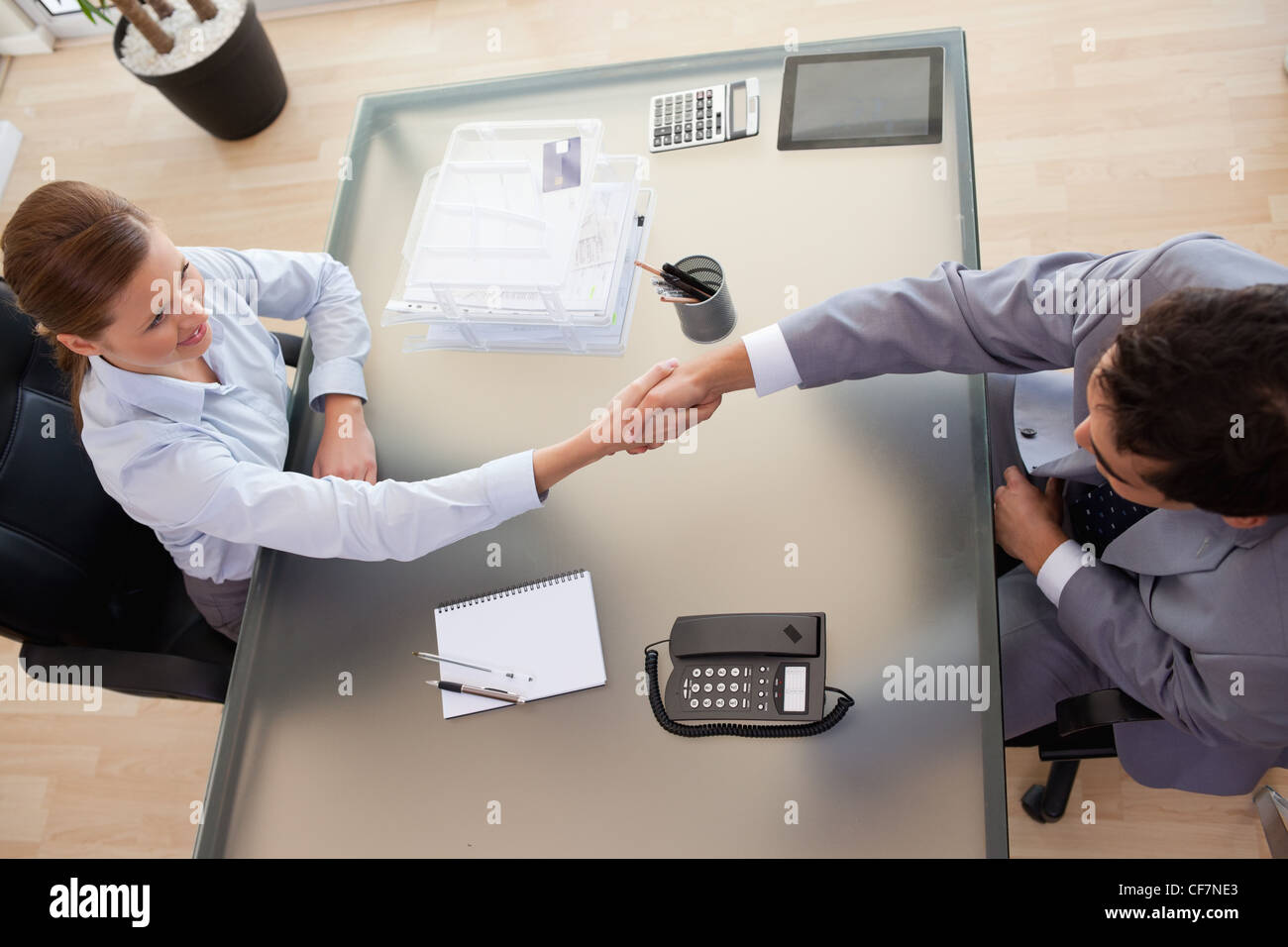 Above view of consultant shaking hands with customer - Stock Image