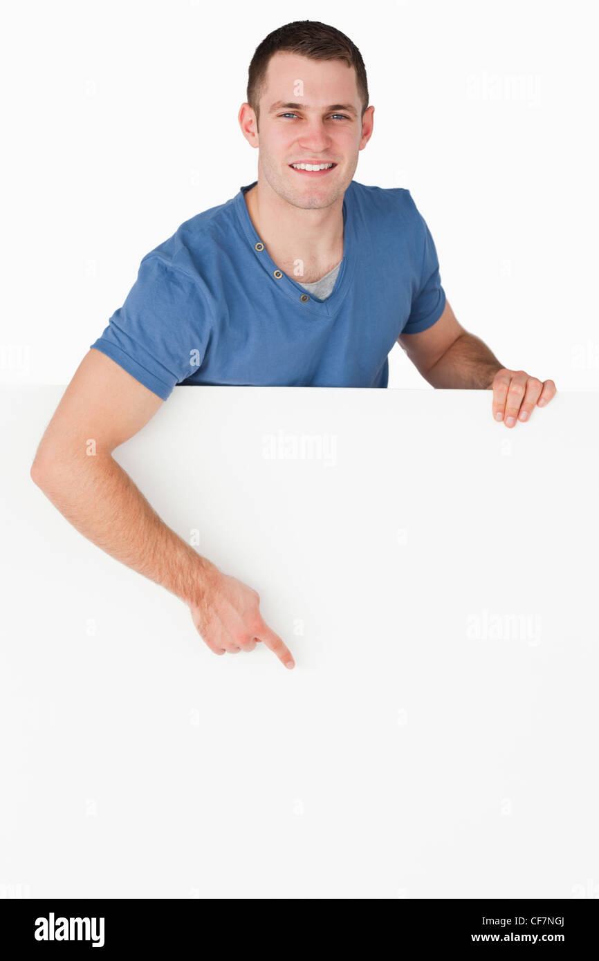 Portrait of a smiling man pointing at a blank panel - Stock Image