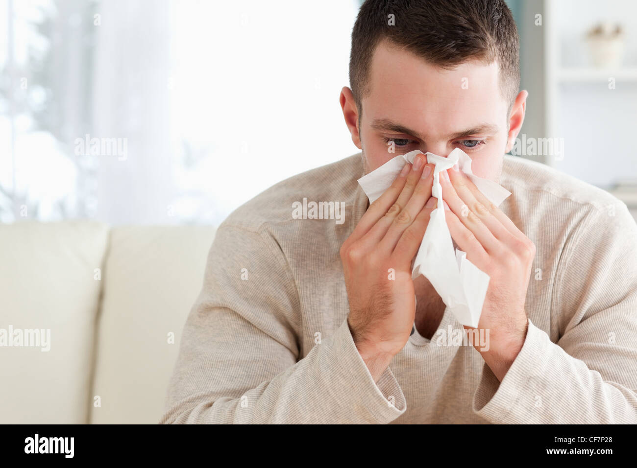 Tired man blowing his nose - Stock Image