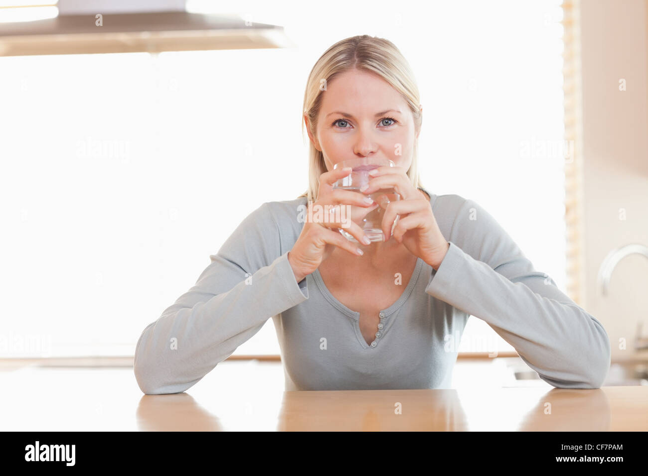 Woman enjoying a sip of water - Stock Image