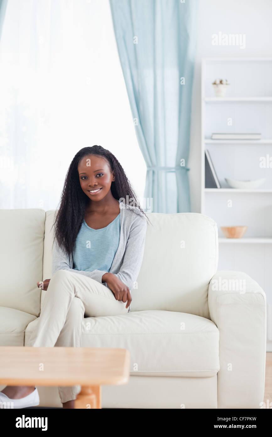 Woman sitting in livingroom - Stock Image