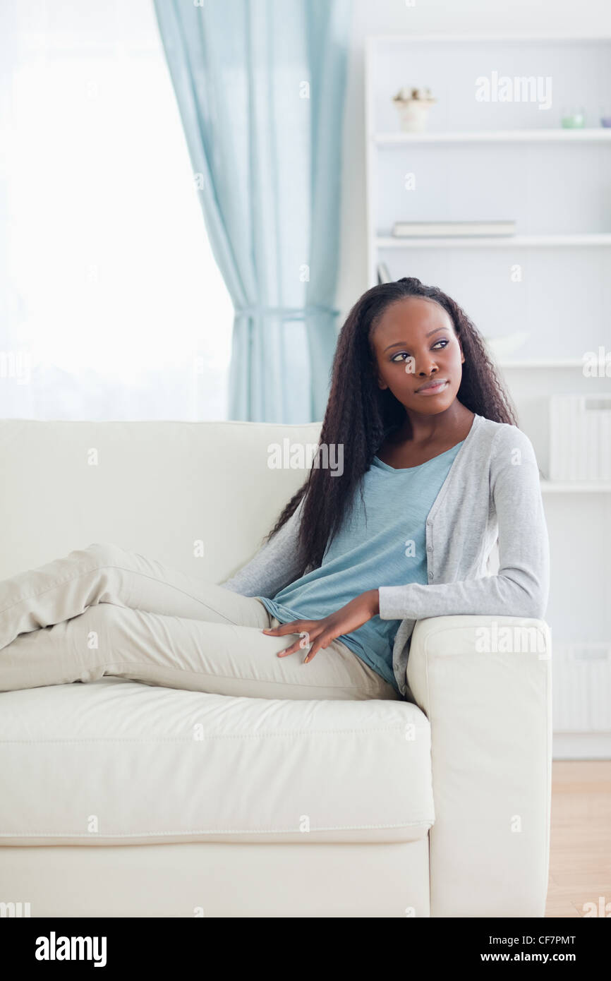 Woman relaxing in livingroom - Stock Image