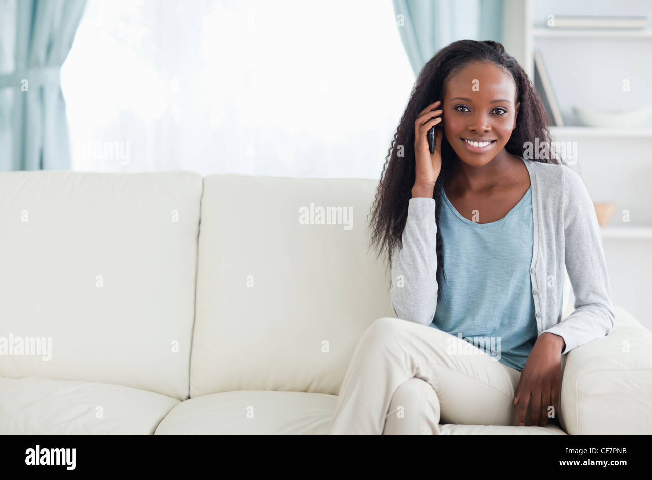 Woman phoning on couch - Stock Image