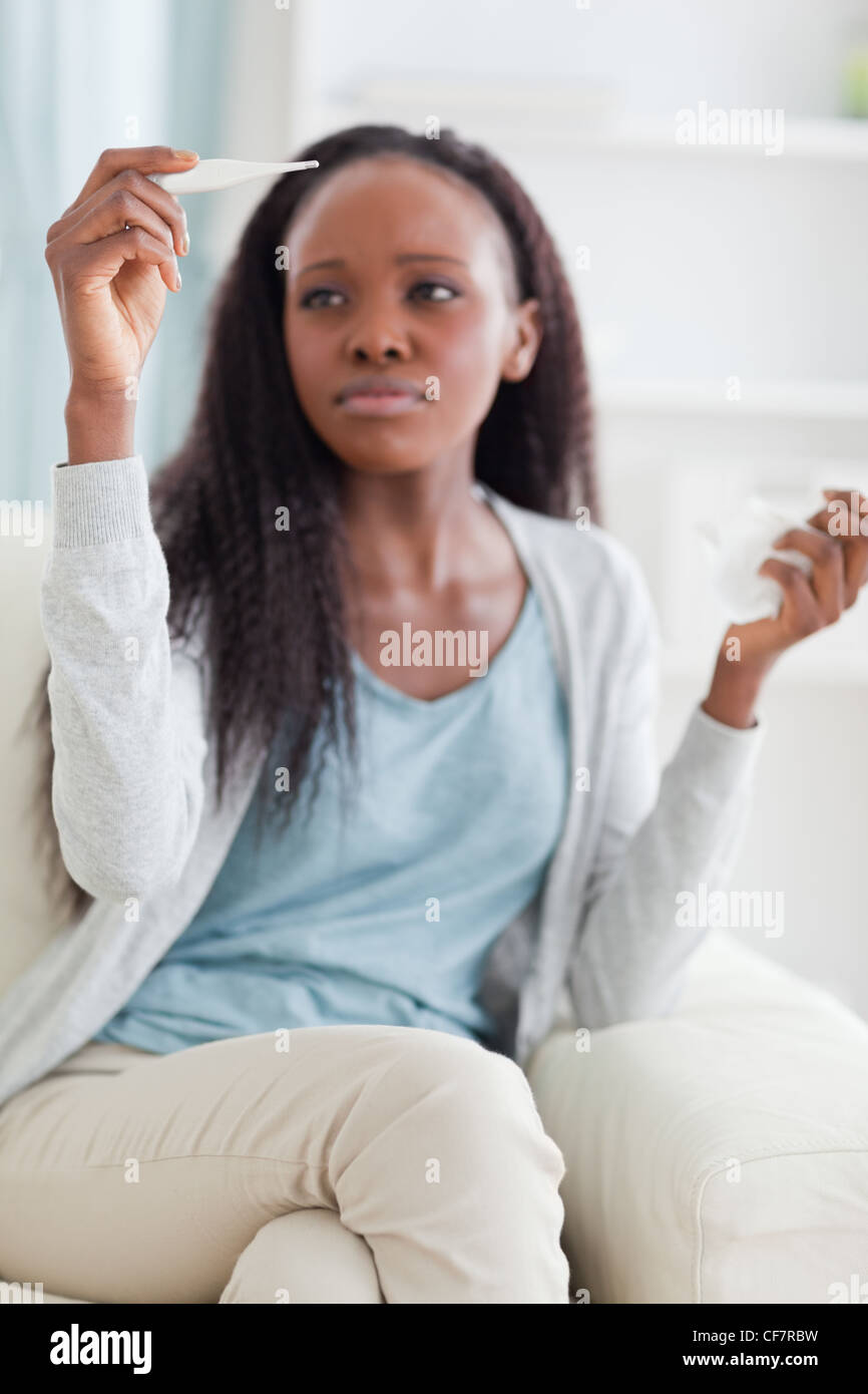 Woman measuring her temperature - Stock Image