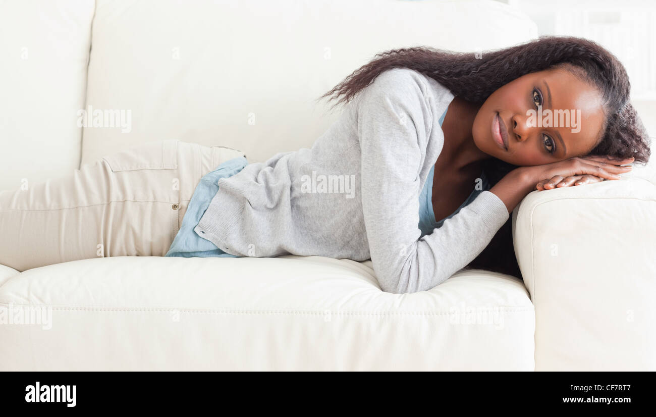 Woman about to take a nap on the sofa - Stock Image