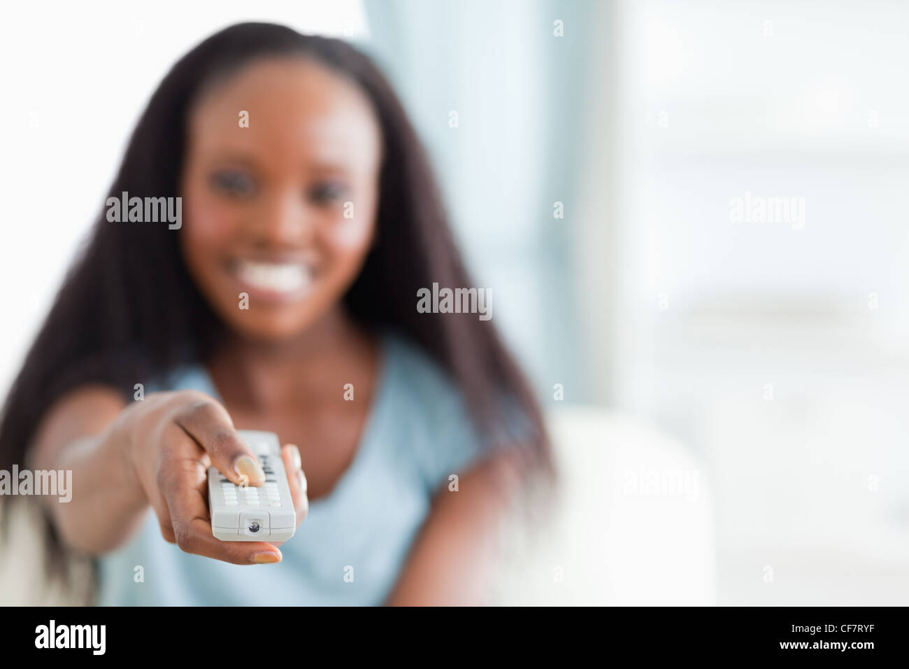 Close up of remote control being used by woman - Stock Image