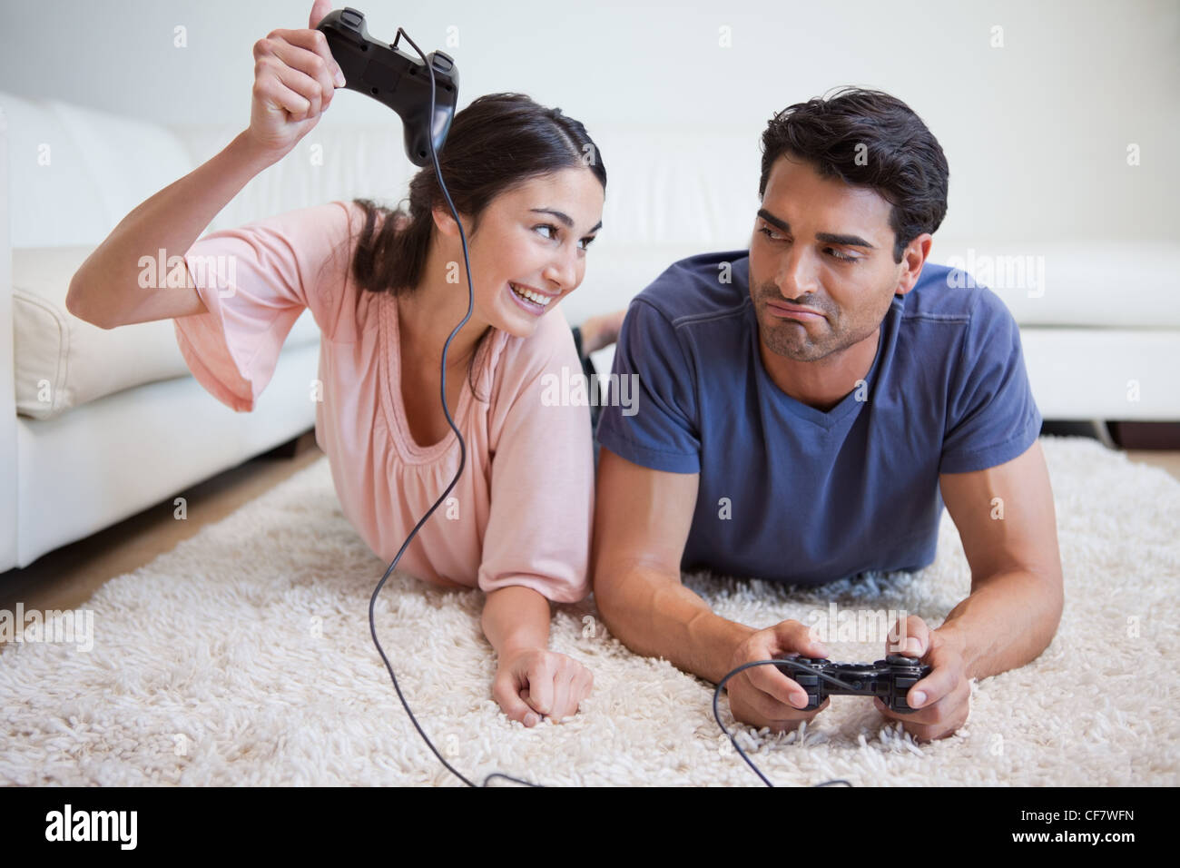 Woman beating her fiance while playing video games - Stock Image
