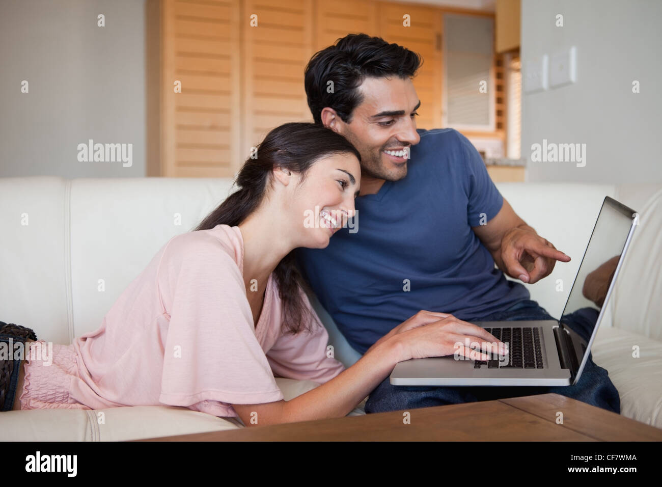 Lovely young couple using a laptop - Stock Image