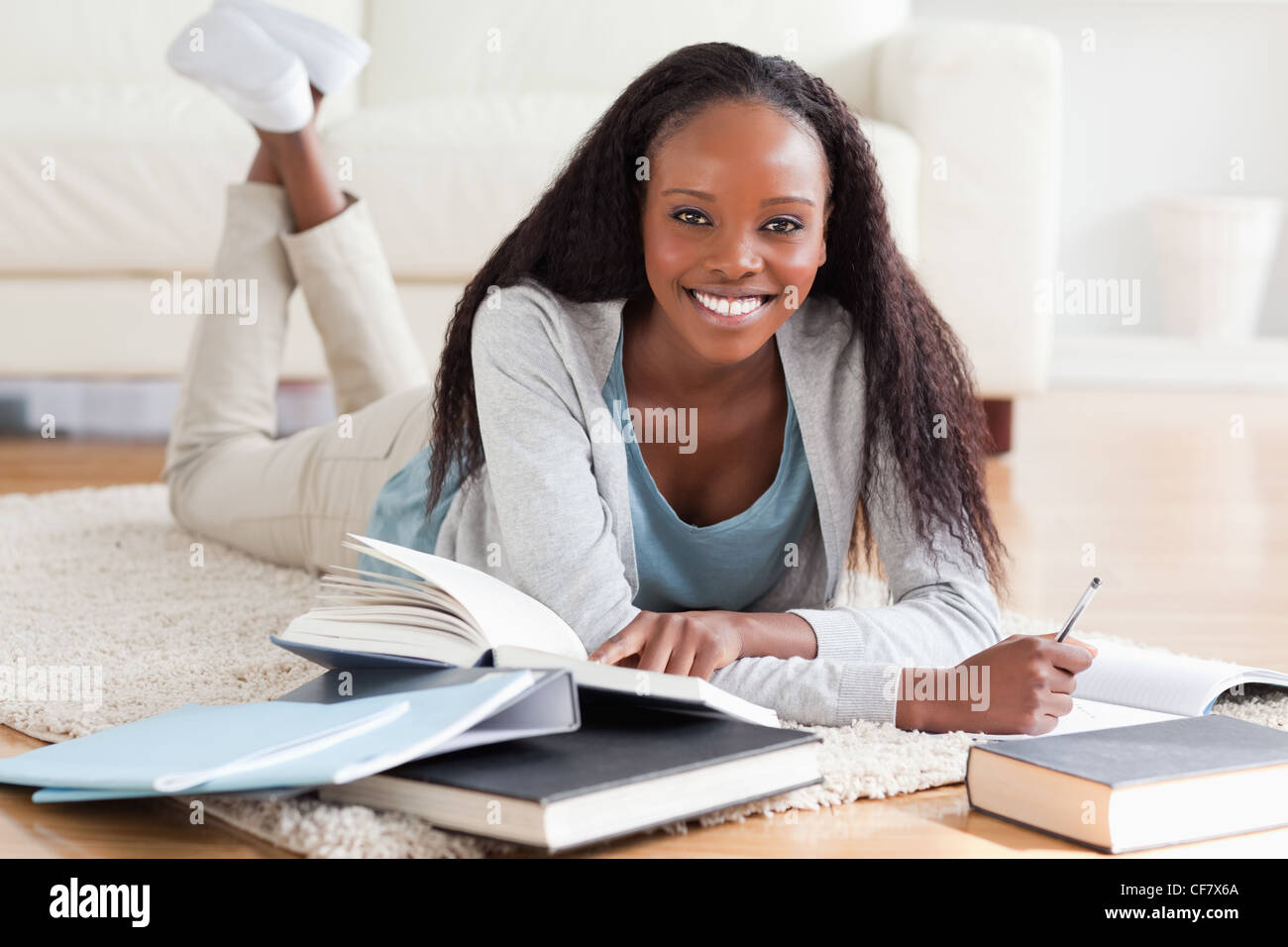 Woman lying on floor working on book review - Stock Image