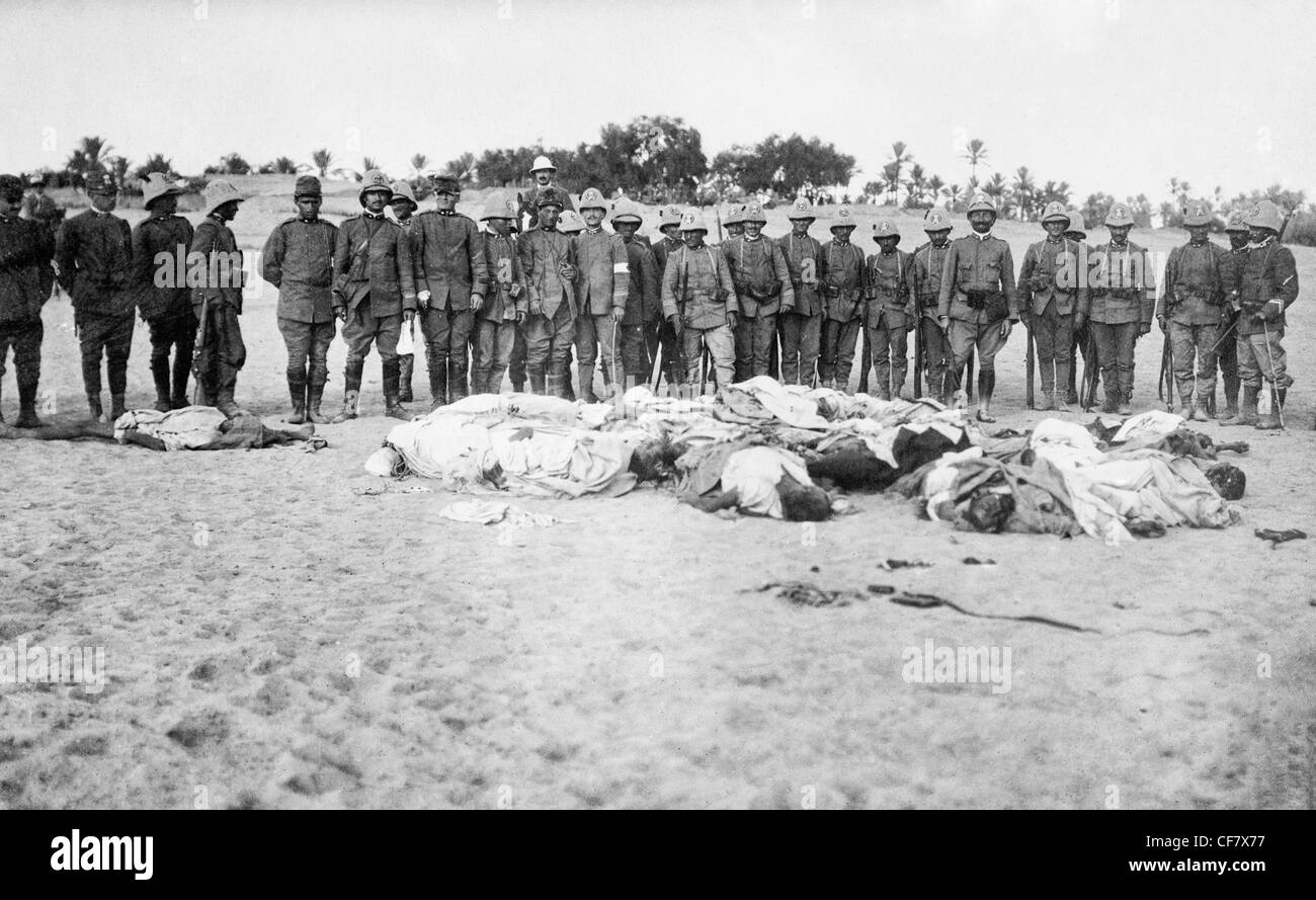 Italian soldiers gathered around dead bodies of Arabs during the Italo Turkish War which took place between September - Stock Image