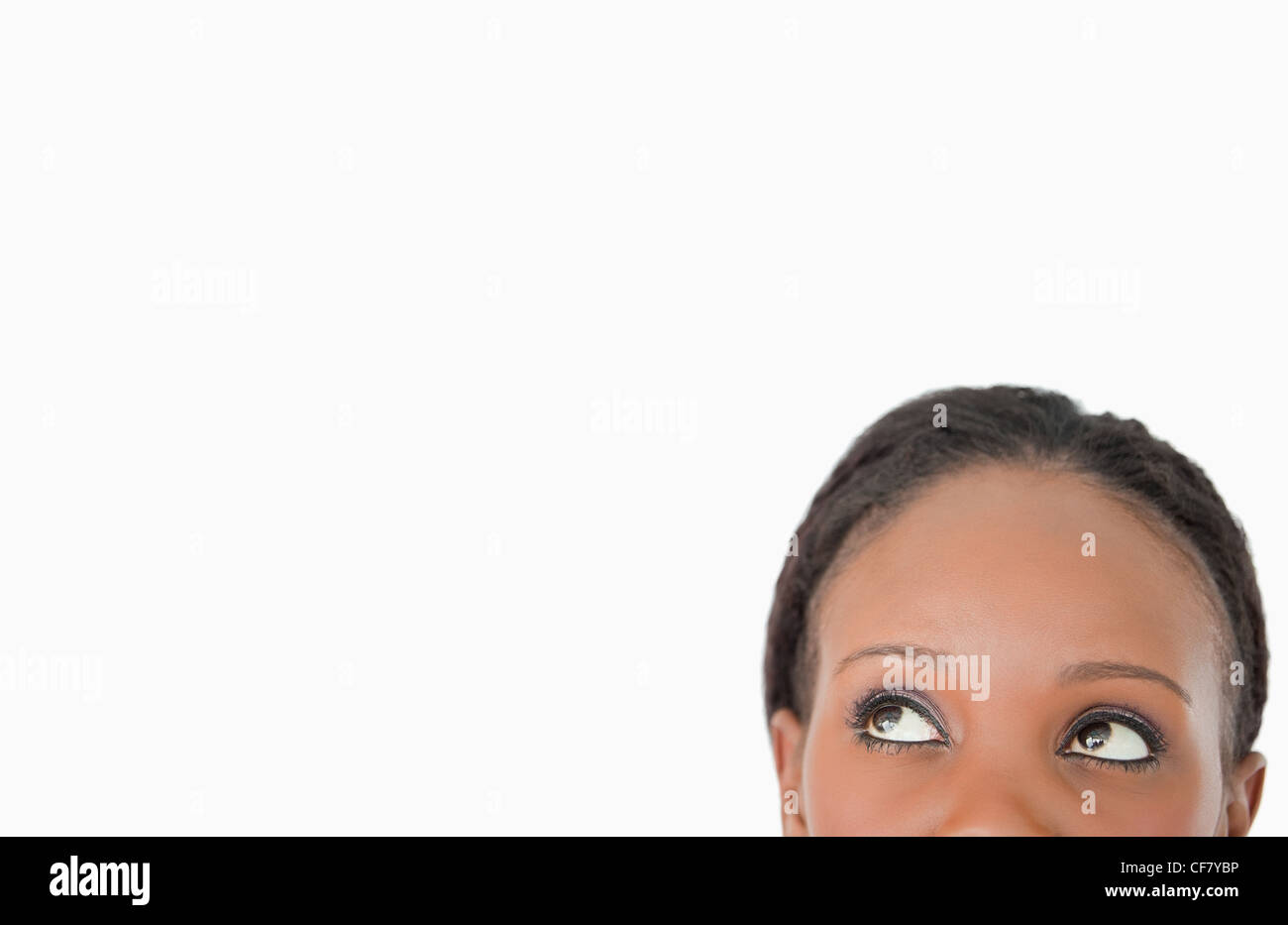 Close up of woman looking upwards diagonally on white background - Stock Image