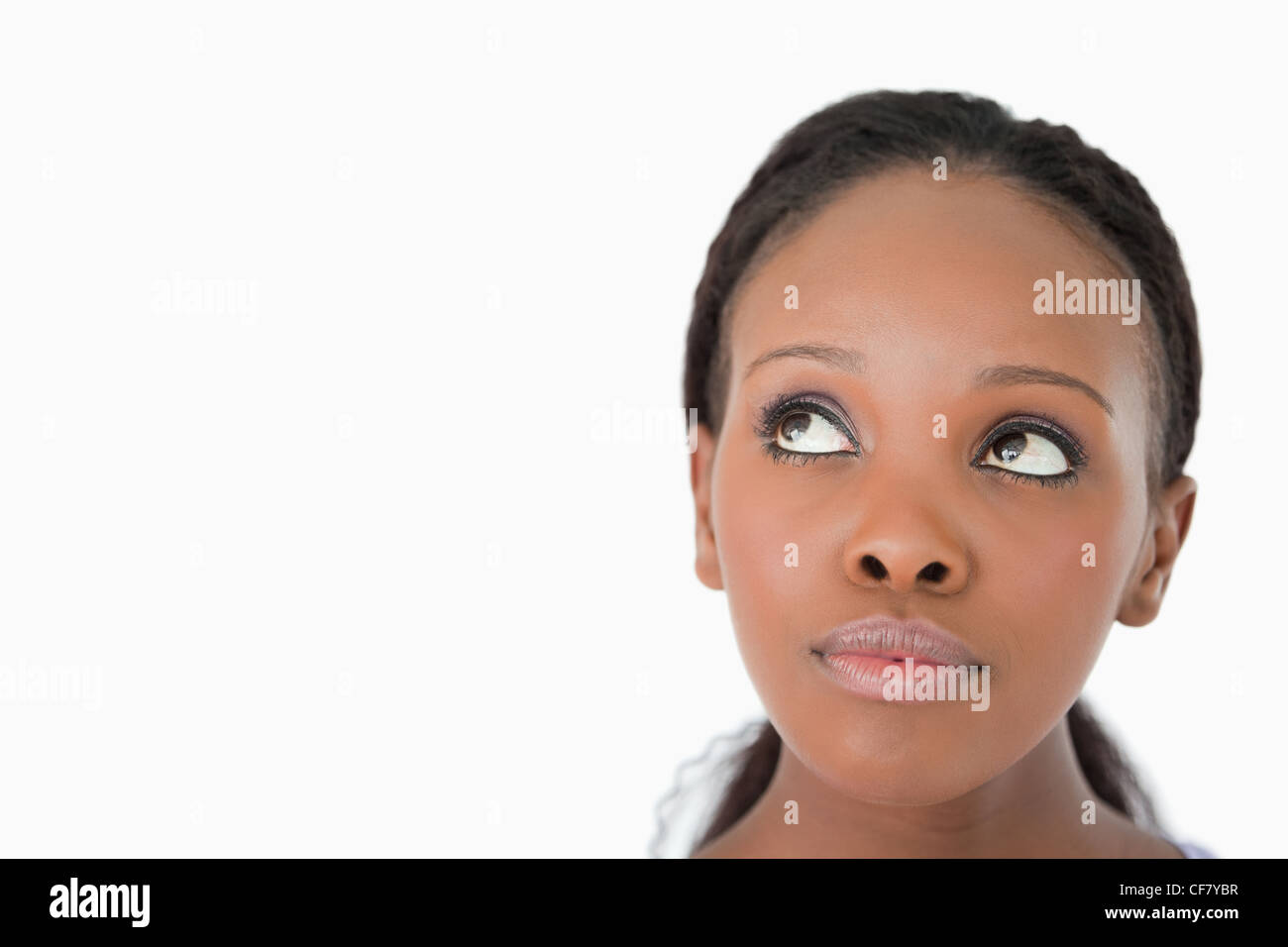Close up of woman's face looking upwards diagonally on white background - Stock Image