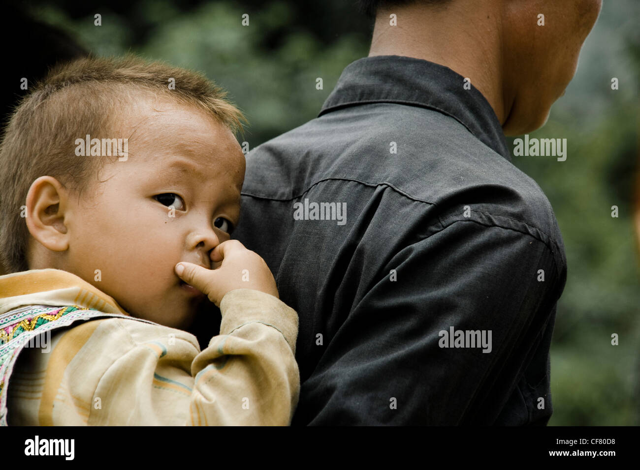 Son rides on fathers back. Sapa market. North Vietnam - Stock Image