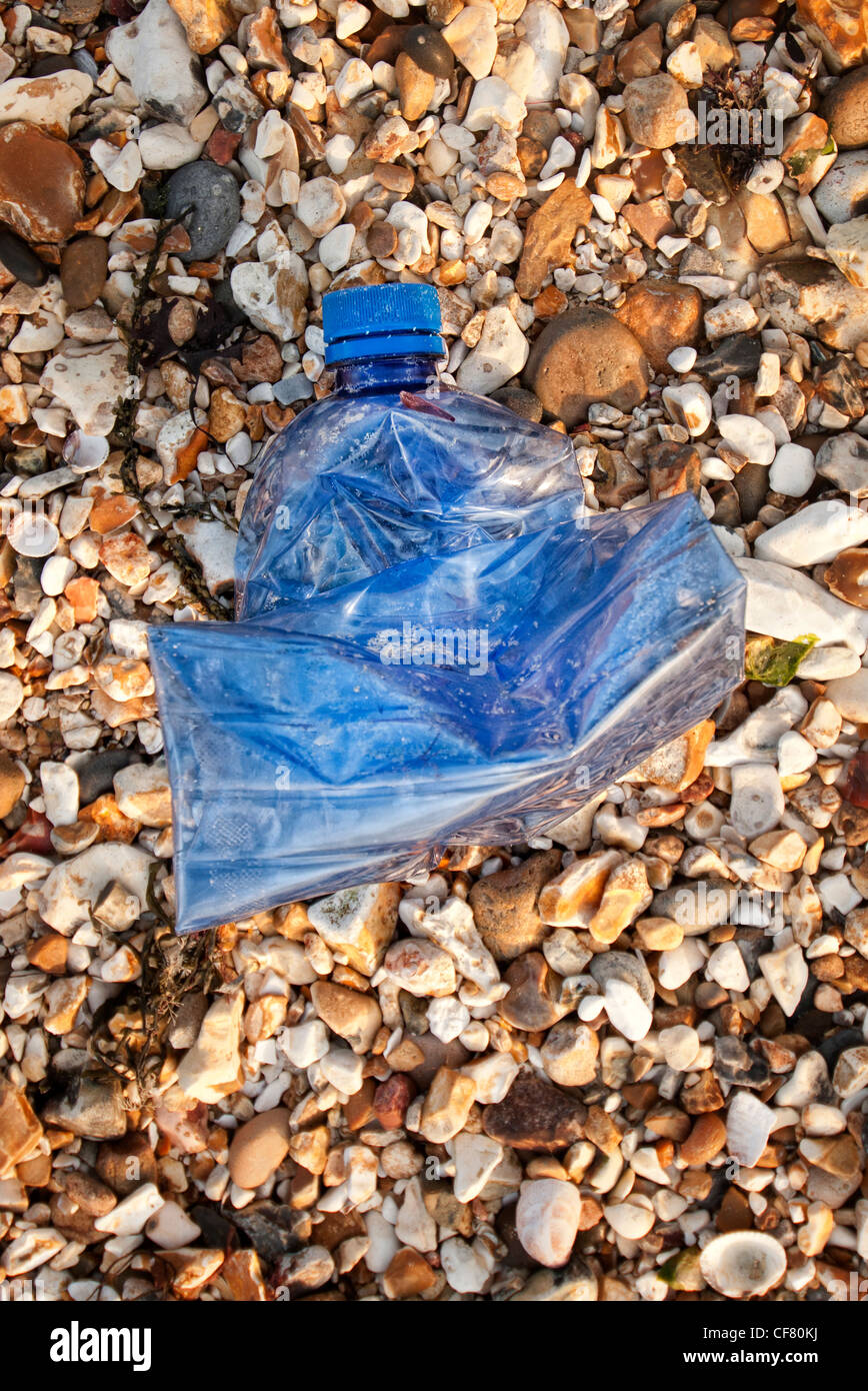blue plastic bottle washed up on the beach - Stock Image