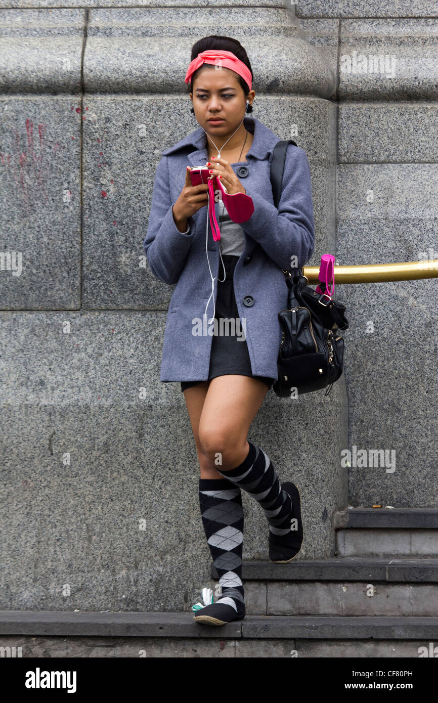 girl with earphones and iPhone outside Flinders Street Station, Melbourne, Australia - Stock Image