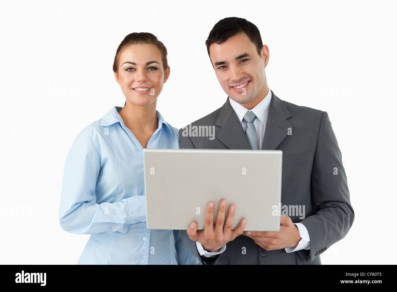 Smiling business partners with laptop - Stock Image