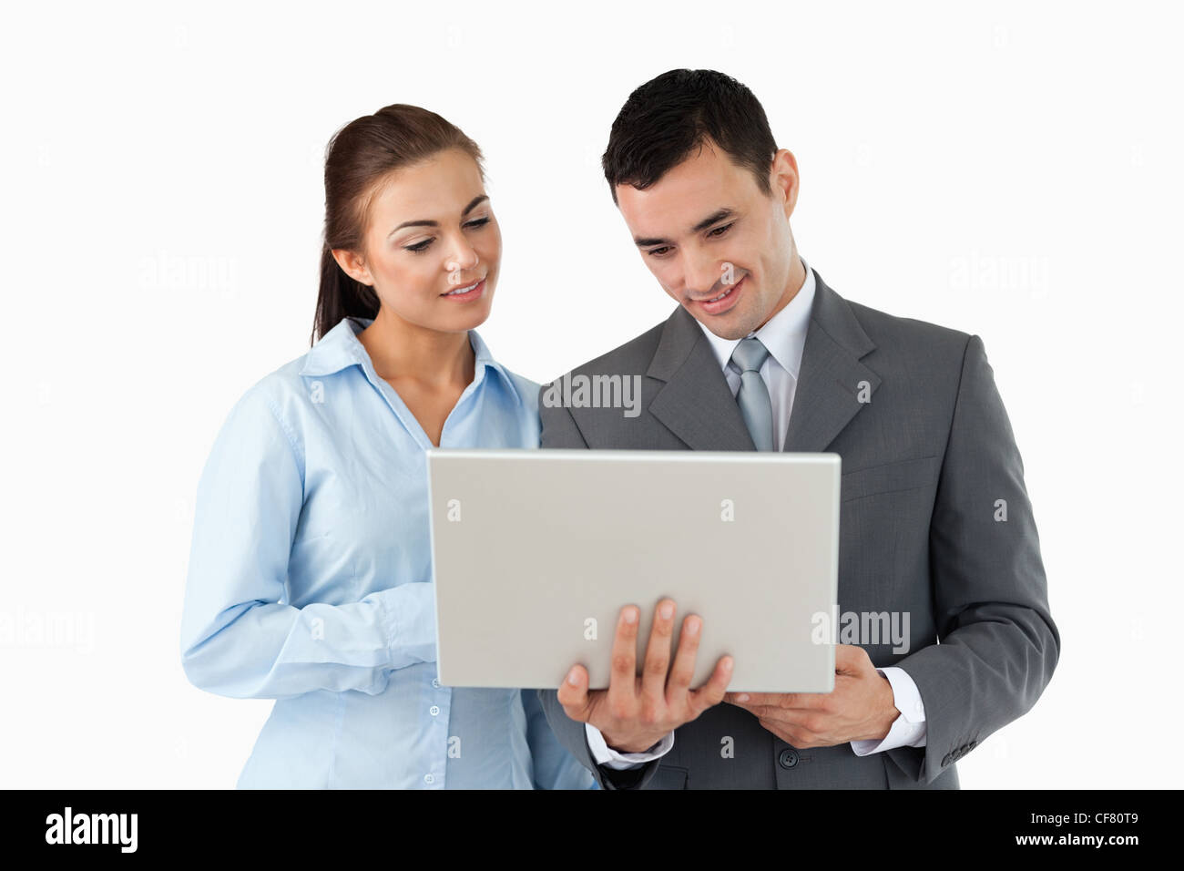 Young business partners looking at laptop - Stock Image