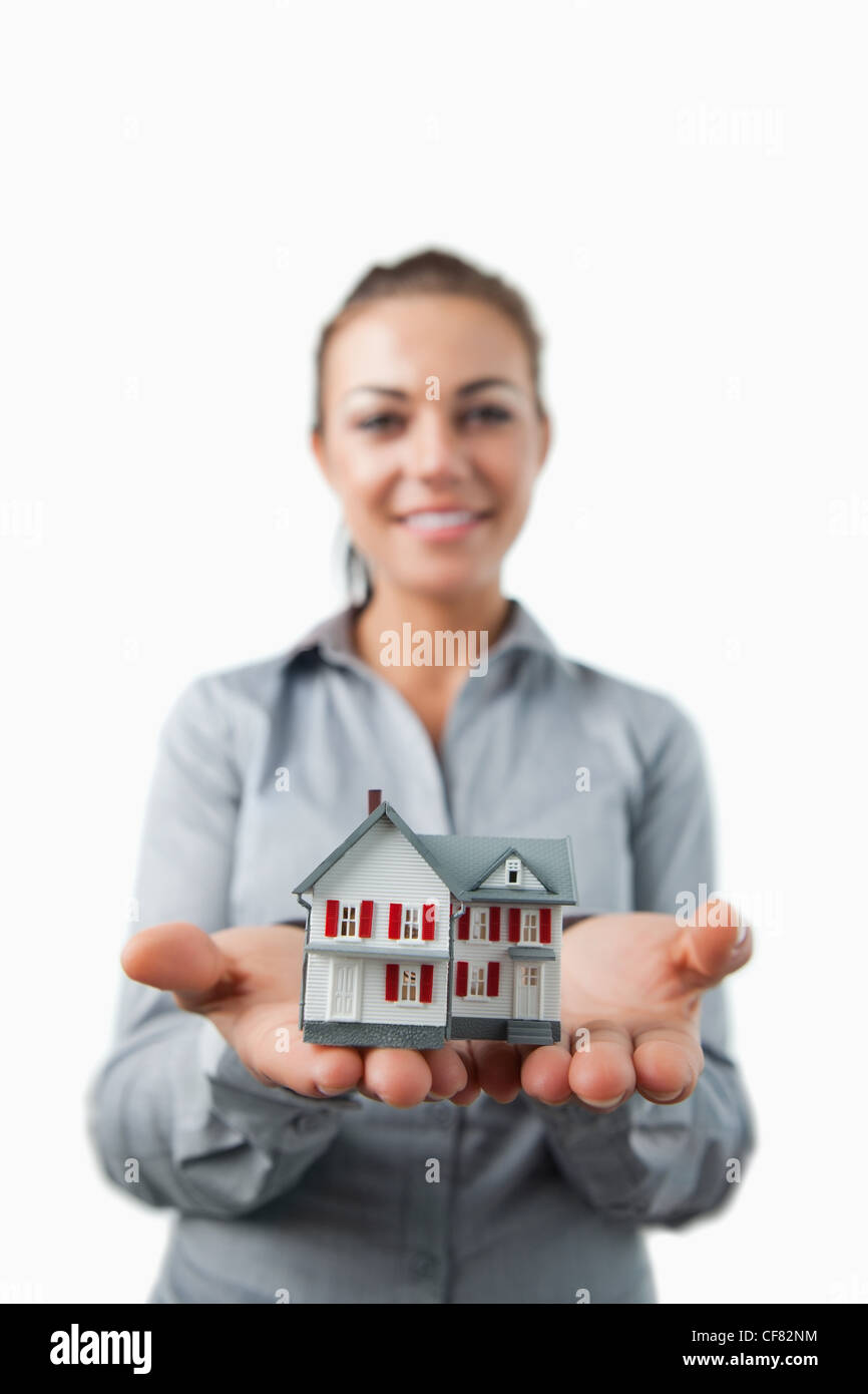 Miniature house being presented by young female estate agent Stock Photo